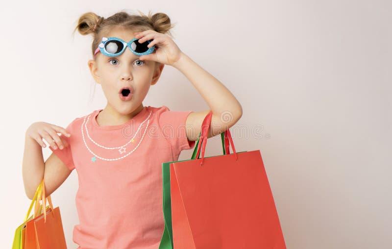Vestido vestindo e óculos de sol da menina bonita que guardam sacos de compras imagens de stock