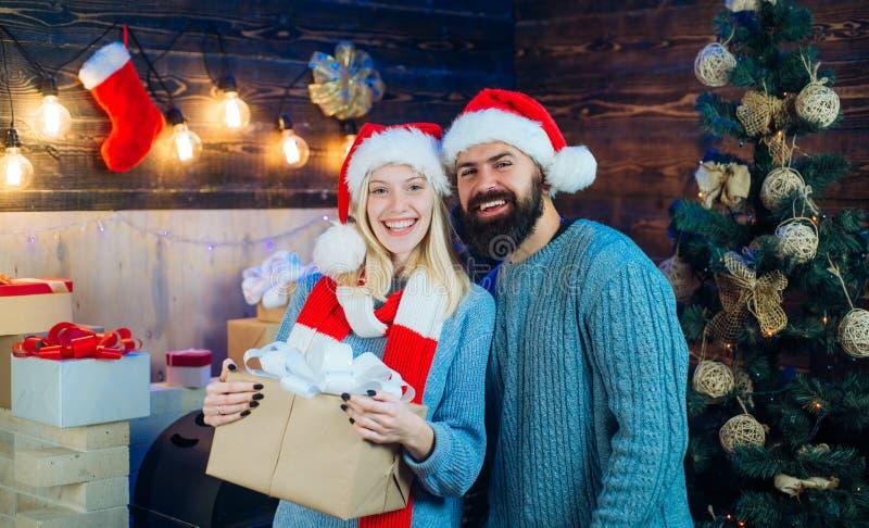 Vestidos de la Navidad Pares de lúpulo sobre fondo de las luces del árbol de navidad Mujer joven linda y hombre hermoso con el so imagen de archivo