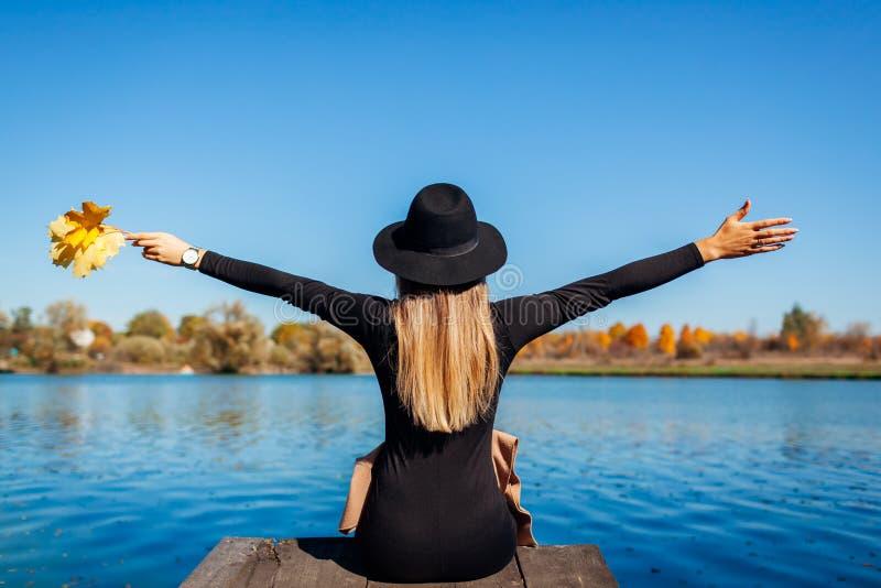 Vestiges d'automne Jeune femme se reposant au bord de la rivière les bras levés sur la jetée photographie stock