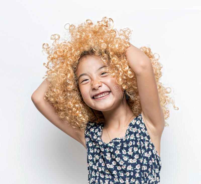 Vestindo uma peruca loura e uma menina engraçada do asiático da expressão facial imagem de stock