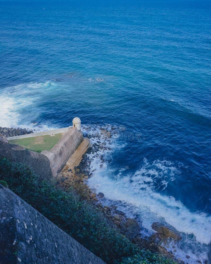 Vestingsmuur en schildwachtdoos over blauwe overzees in Oud San Juan, Puerto Rico royalty-vrije stock foto's