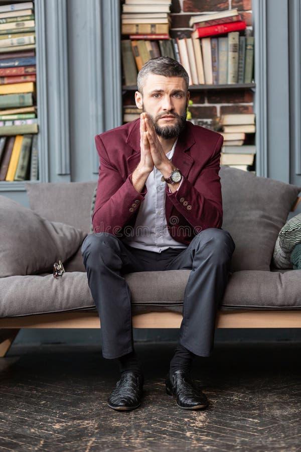 Vestir à moda considerável do homem de negócios escuro - revestimento vermelho que senta-se no sofá fotografia de stock