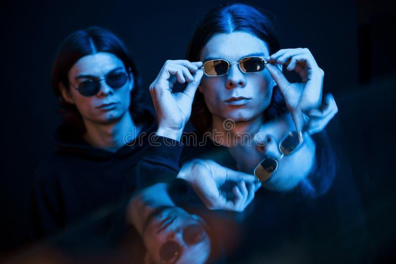 Vestir óculos de sol Retrato de irmãos gêmeos Estúdio fotografado em estúdio escuro com luz neon foto de stock