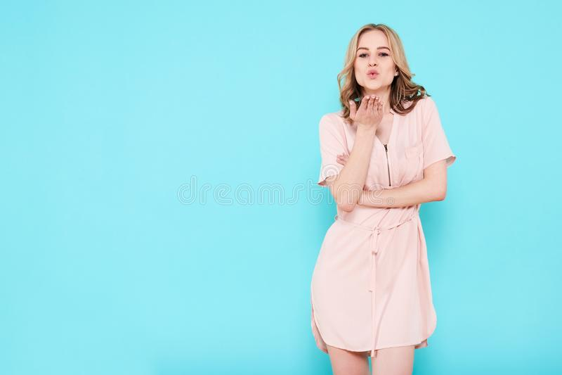 vestir atrativo novo da mulher pálido - vestido cor-de-rosa do verão isolado sobre o fundo azul pastel, fundindo um beijo para a  imagem de stock