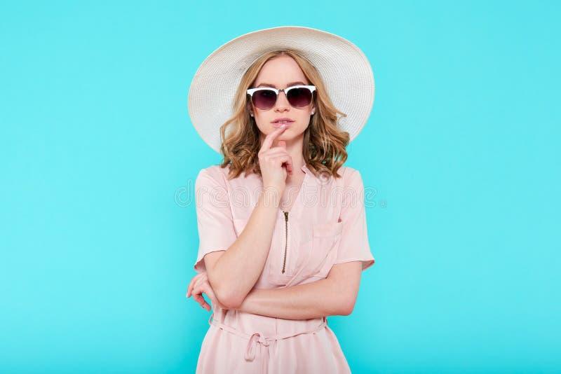 Vestir atrativo novo elegante da mulher pálido - vestido do verão, chapéu de palha cor-de-rosa e óculos de sol, pensando sobre su fotografia de stock