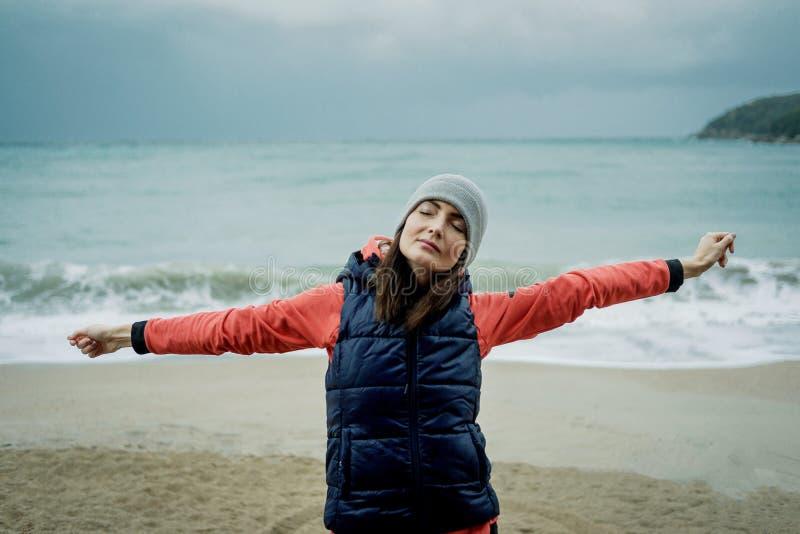 Vestir da jovem mulher esportes investe o exercício pelo mar do inverno foto de stock