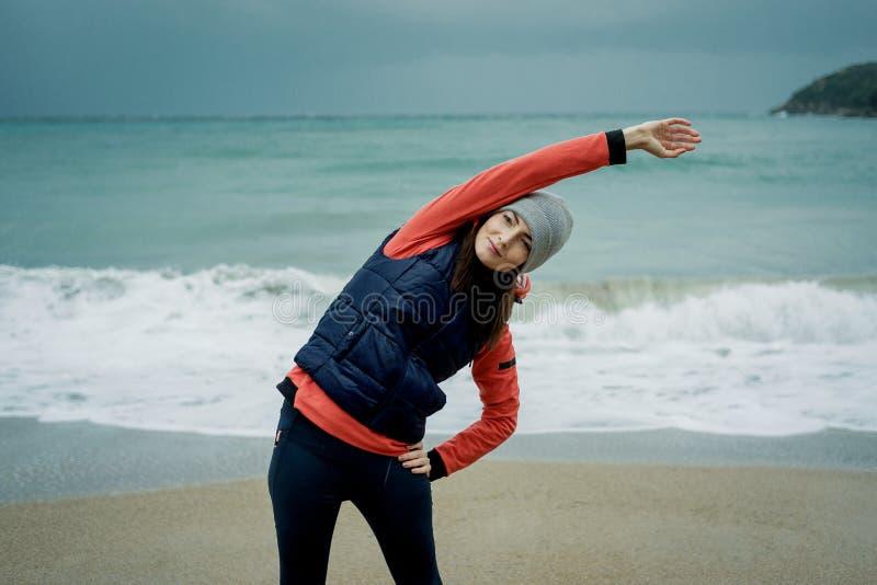 Vestir da jovem mulher esportes investe o exercício pelo mar do inverno fotografia de stock