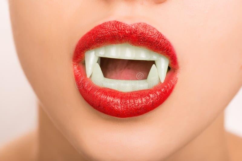Vestir da moça compõe e falsifica os dentes do vampiro imagem de stock royalty free