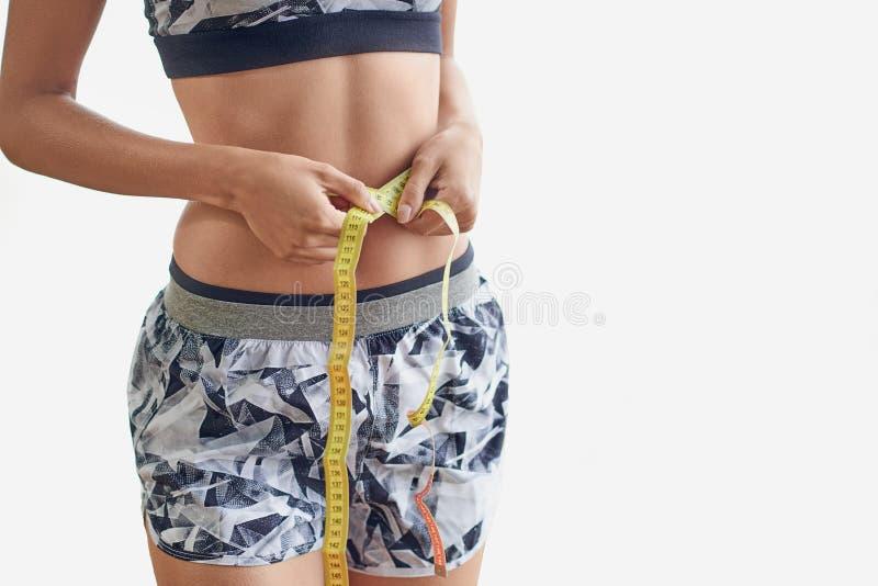 Vestir delgado da mulher esportes na moda equipa a medição de sua cintura imagem de stock