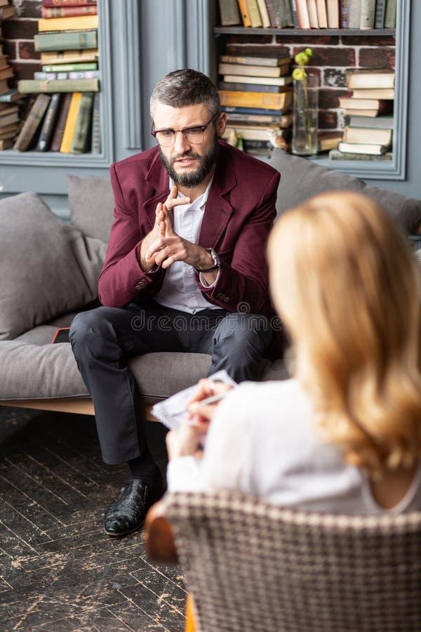 Vestir do homem de negócios escuro - revestimento vermelho que compartilha de suas preocupações com o terapeuta foto de stock royalty free