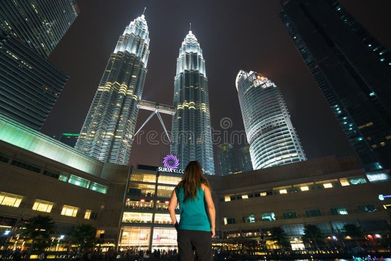 Vestir do viajante da jovem mulher ocasional aprecia fins de semana de surpresa Olhando afastado à construção em Kuala Lumpur, Ma fotografia de stock