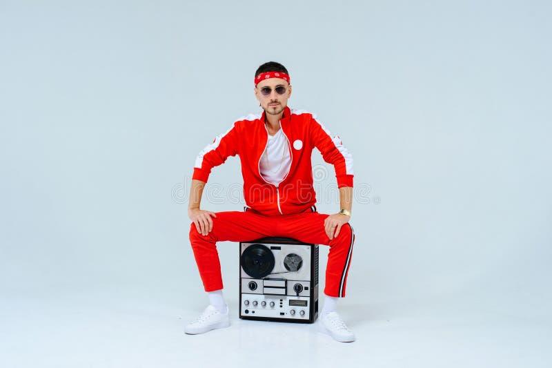 Vestir elegante alegre do homem esportes vermelhos sere o assento com um gravador retro estilo orgulhoso e bem sucedido 90 do ` s imagem de stock