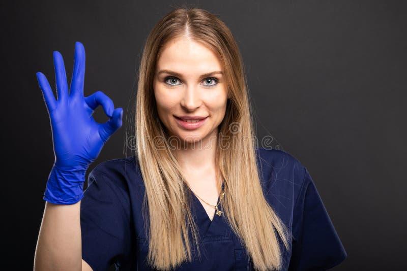Vestir fêmea bonito do dentista esfrega mostrar o gesto aprovado fotografia de stock royalty free