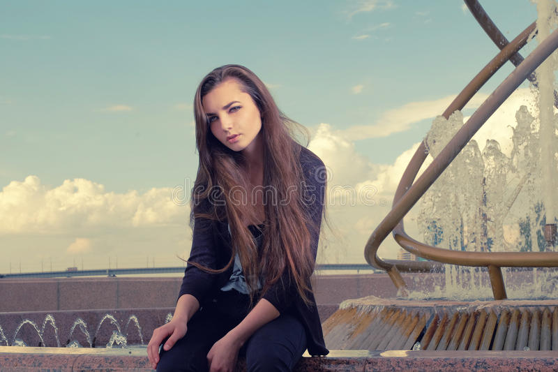 Vestir que de jovem mulher um desgaste preto se está sentando por uma fonte na cidade e se está olhando a câmera, conceito do olh foto de stock royalty free