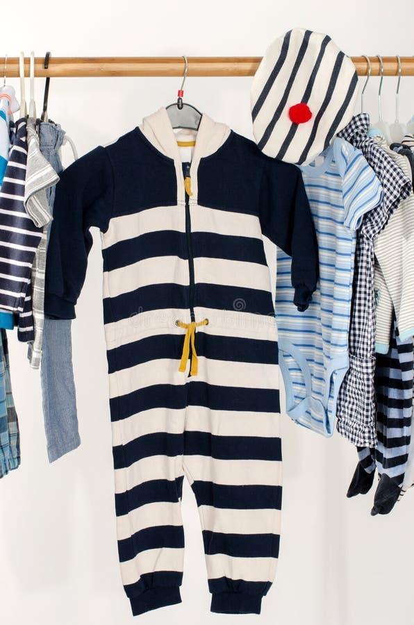 Vestire il gabinetto con il bambino ha barrato i vestiti sistemati sui ganci fotografie stock libere da diritti