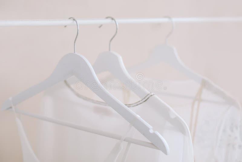 Vestiti bianchi su un gancio Concetto di minimalismo Installi dei vestiti da sposa dalle donne sull'i ganci di legno, il fondo di immagine stock libera da diritti