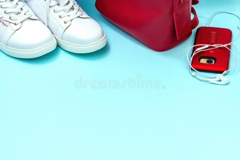 Vestiti casuali di sport di vista superiore messi per la giovane donna Accessori di colori bianchi e rossi sopra fondo blu pastel fotografia stock libera da diritti