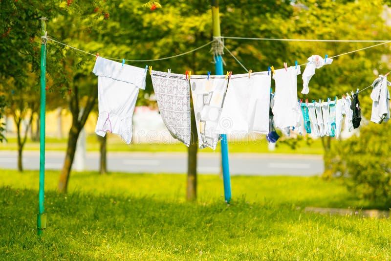 Vestiti che si asciugano in aria fresca sui fili stendiabiti immagini stock