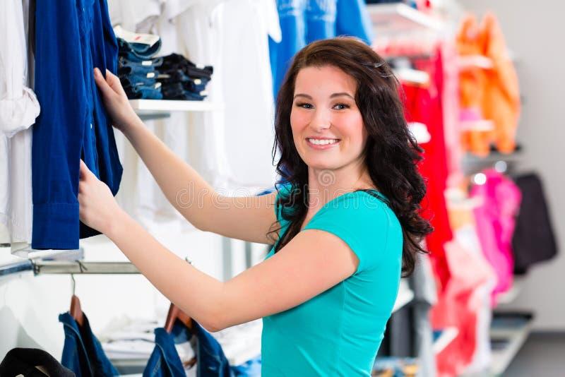 Vestiti d'acquisto della donna in negozio immagine stock