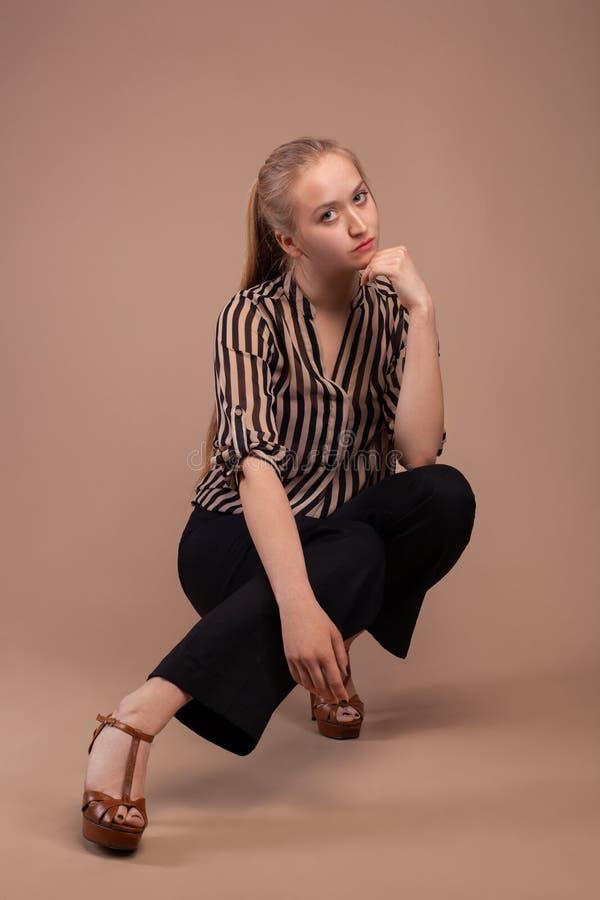 Vestiti d'uso di modo della donna su fondo marrone fotografie stock libere da diritti