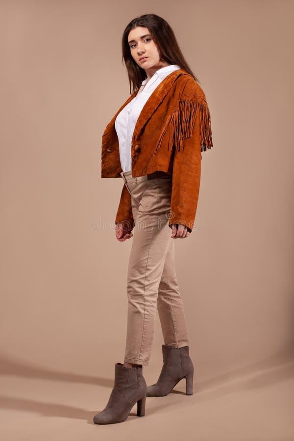 Vestiti d'uso di modo della donna su fondo marrone immagini stock