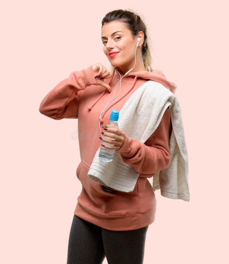 Vestiti d'uso di sport della giovane donna sopra fondo rosa fotografia stock libera da diritti