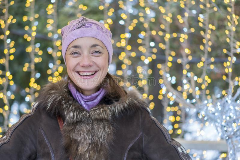 vestiti d'uso sorridenti di inverno della giovane donna che celebrano il Natale alla via con le stelle filante Spazio vuoto fotografie stock
