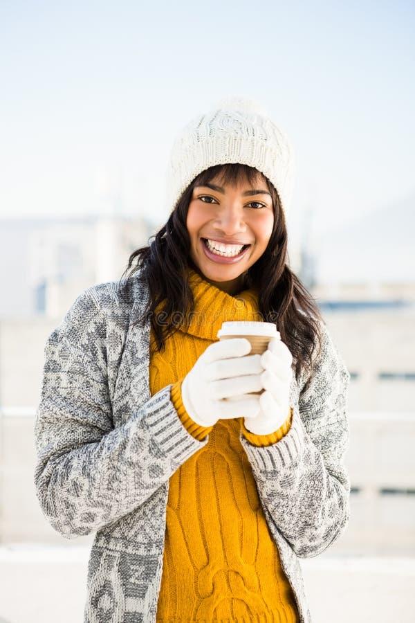 Vestiti d'uso sorridenti e tenuta di inverno della donna del caffè fotografia stock libera da diritti