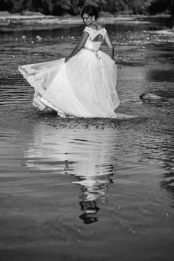 Vestiti da sposa sposa graziosa in acqua fotografie stock