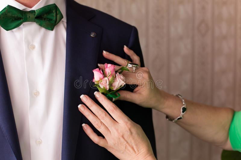 Vestiti dalla madre allo sposo un occhiello immagine stock
