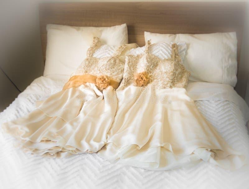 Vestiti dalle domestiche delle spose sul letto fotografie stock