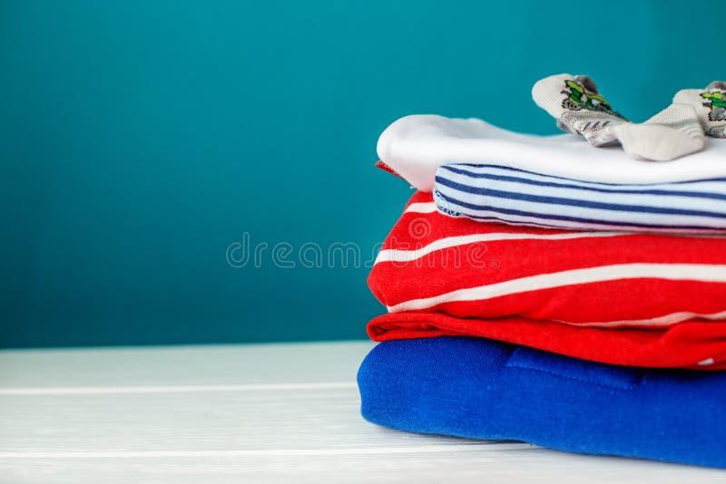 Vestiti del ` s dei bambini impilati in un mucchio Concetto dei neonati, maternità, cura, stile di vita fotografia stock libera da diritti