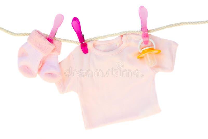 Vestiti della neonata che appendono sulla corda immagini stock libere da diritti