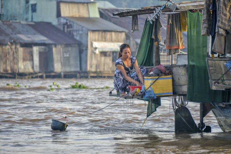 Vestiti di lavaggio della donna nel fiume di mekong fotografie stock