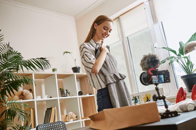 Vestiti di modo Vista laterale del blogger femminile sveglio che registra nuovo video circa il vestito per il suoi vlog e sorride fotografia stock libera da diritti