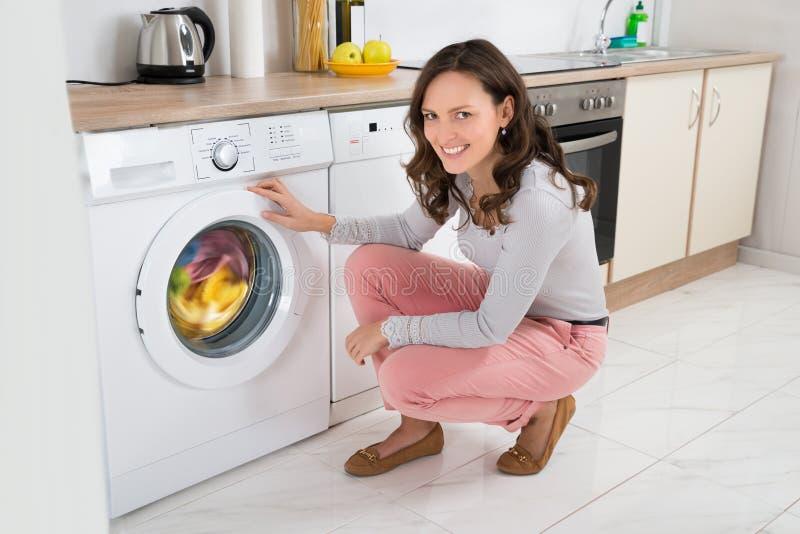 Vestiti di pulizia della donna in lavatrice immagini stock