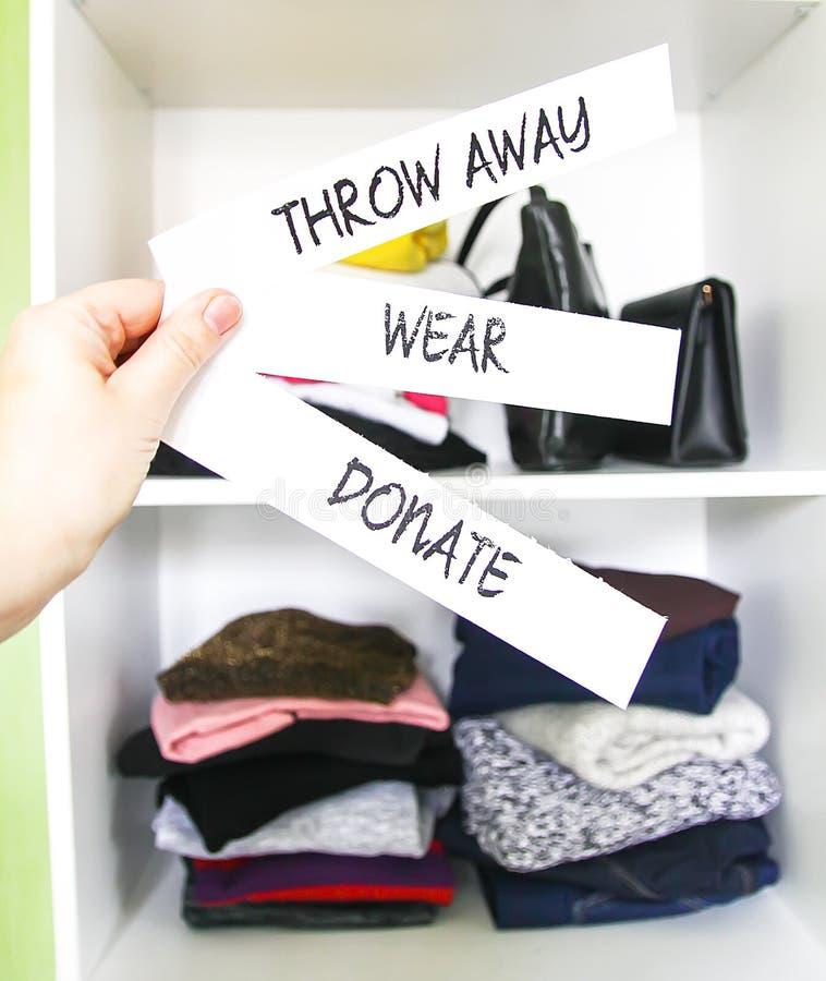 Vestiti diversi nell'armadio domestico con note di carta Piccola organizzazione spaziale Il contrasto tra ordine e disordine Vert fotografia stock