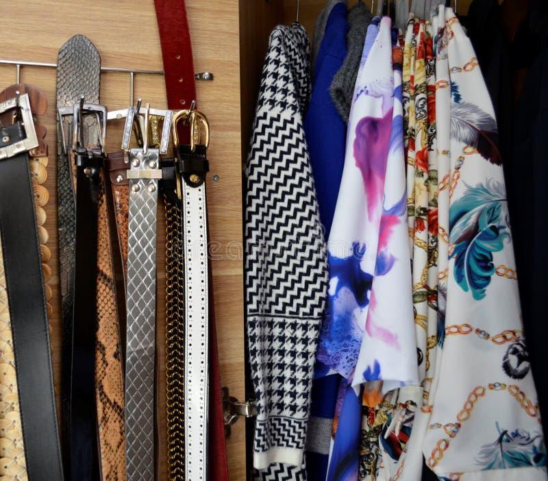 Vestiti e cinghie in guardaroba, fine su fotografia stock libera da diritti