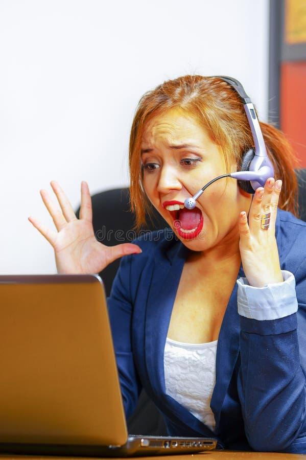 Vestiti e cuffia avricolare d'uso dell'ufficio della giovane donna attraente che si siedono dallo scrittorio che esamina schermo  immagine stock