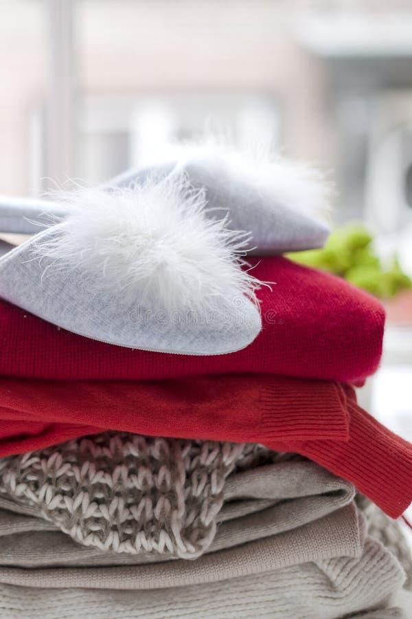 Vestiti e pantofole caldi differenti vicino alla finestra Maglioni per l'autunno e l'inverno Spazio libero per testo immagine stock libera da diritti