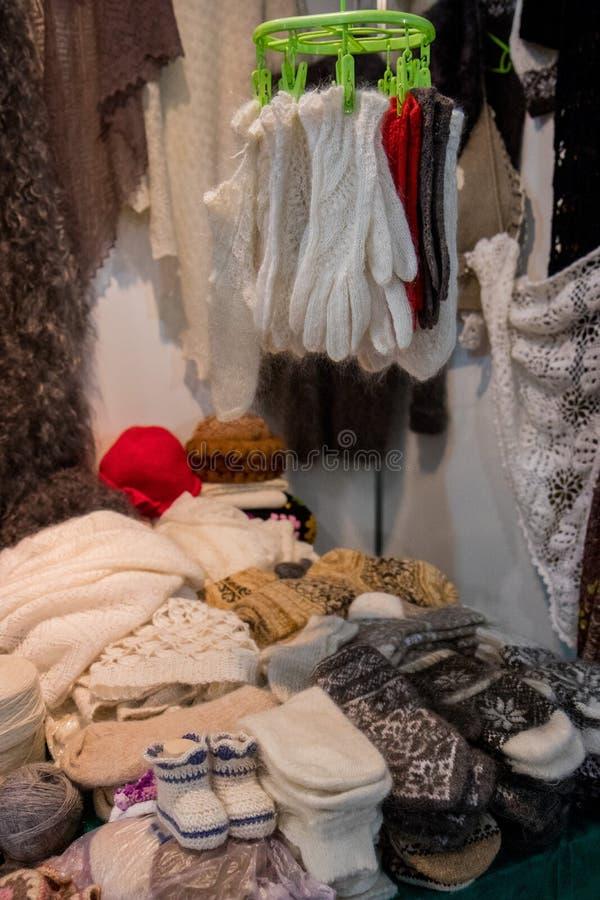 Vestiti lavorati a maglia Guanti e calzini tricottati con gli ornamenti variopinti da vendere sul mercato immagini stock