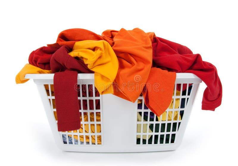 Vestiti nel cestino di lavanderia. Rosso, arancione, colore giallo. fotografia stock