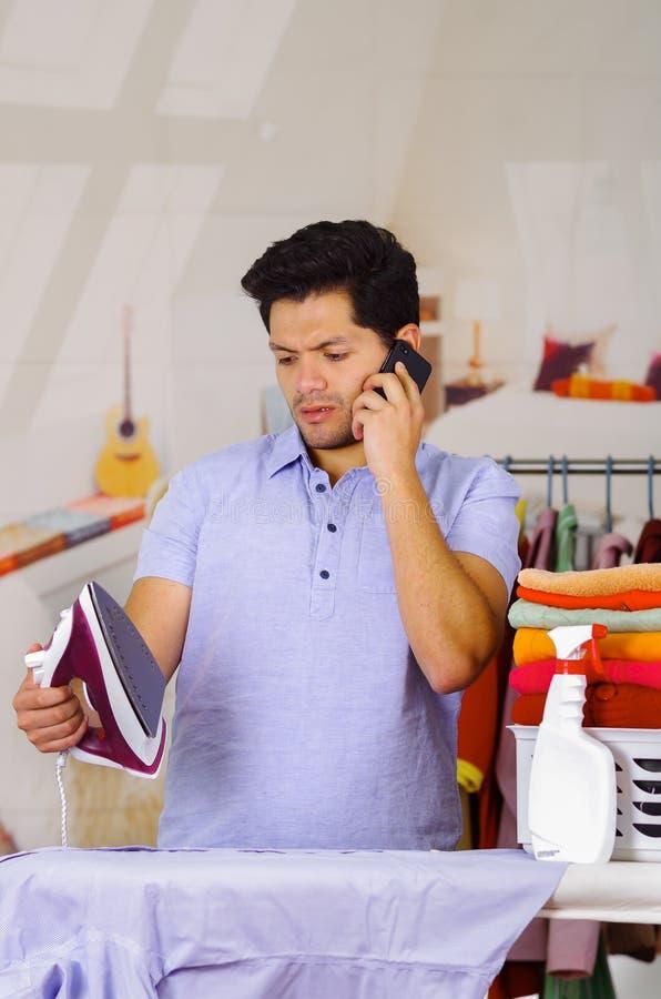 Vestiti rivestenti di ferro bei del giovane sulla tavola da stiro mentre sta utilizzando il suo cellulare fotografie stock