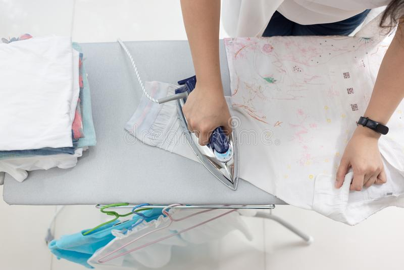 Vestiti rivestenti di ferro della donna facendo uso di ferro sulla tavola da stiro a casa, principale vi fotografia stock libera da diritti