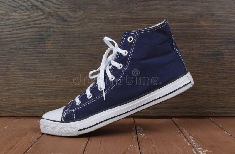 Vestiti, scarpe ed accessori - fondo di legno dei gumshoes di vista laterale una immagine stock libera da diritti