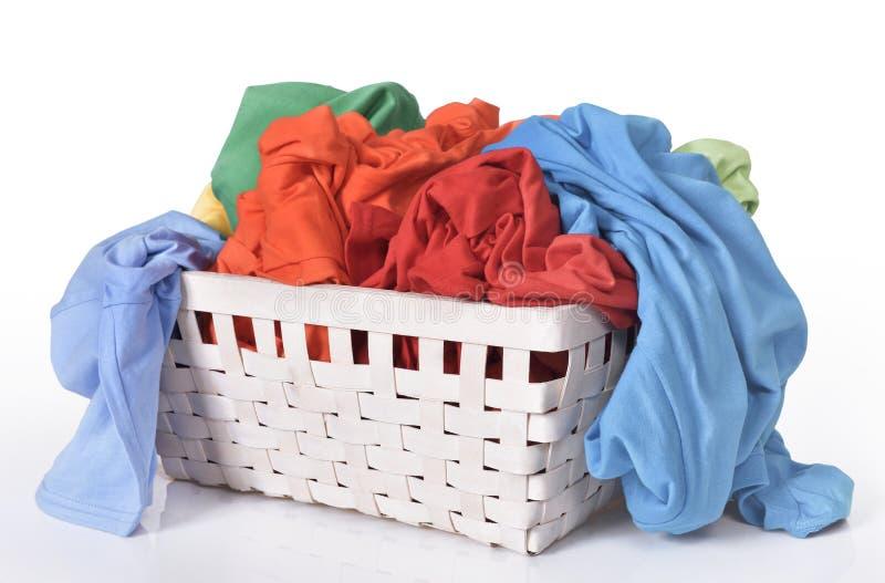 Vestiti sporchi variopinti nel canestro di lavanderia fotografia stock