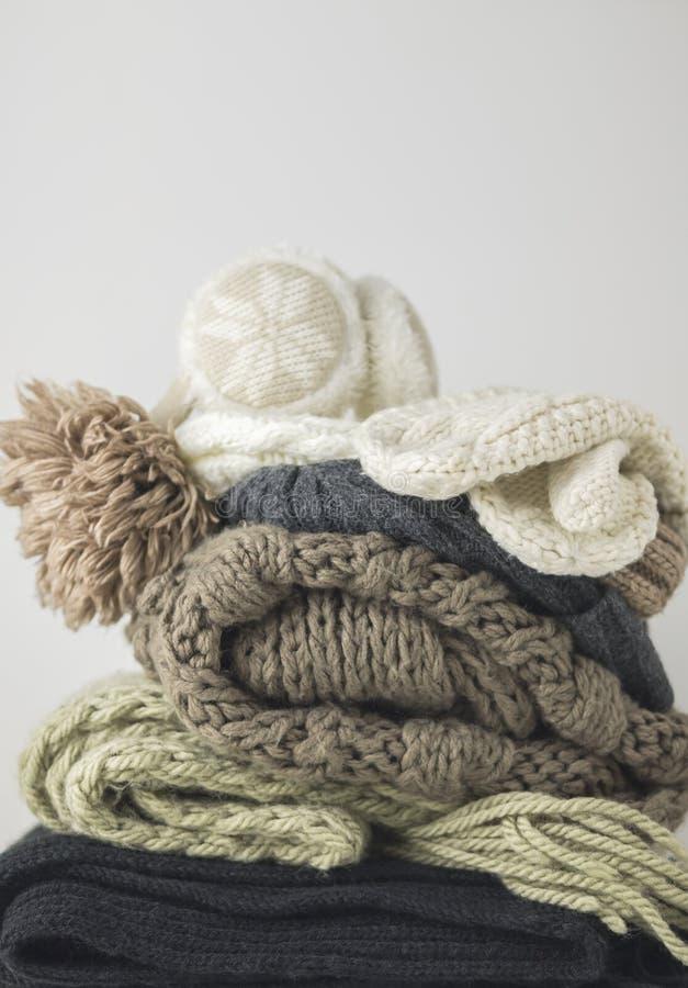 Vestiti tricottati di lana caldi di autunno e di inverno, piegati in un mucchio su una tavola bianca Maglioni, sciarpe, guanti, c immagine stock libera da diritti