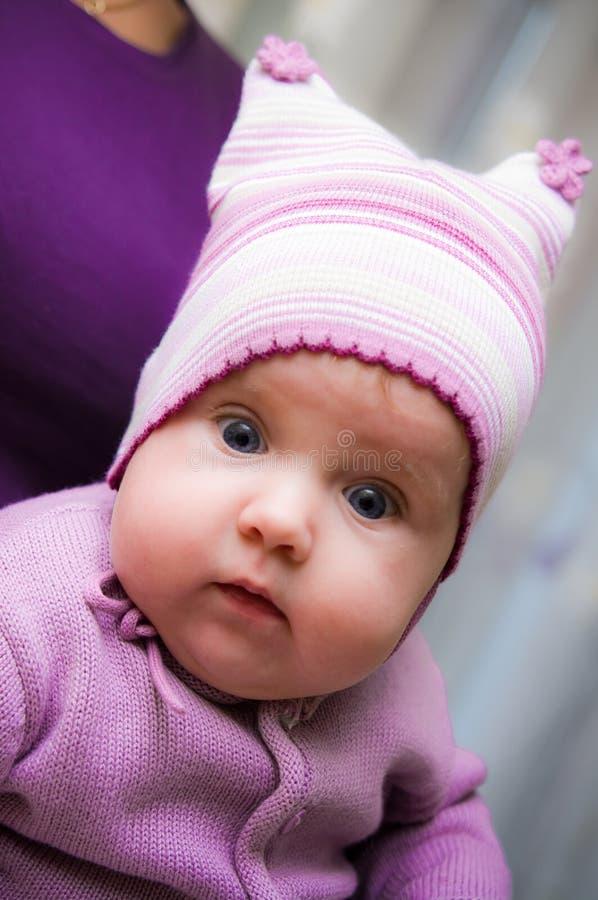 Vestiti viola d'uso della neonata sveglia fotografia stock