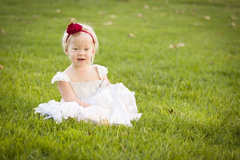 Vestito bianco d'uso dalla bambina adorabile in un campo di erba fotografie stock