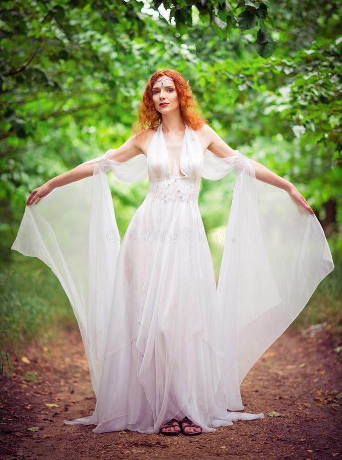 Vestito bianco d'uso dalla bella della testarossa donna dell'elfo in un giardino fotografia stock